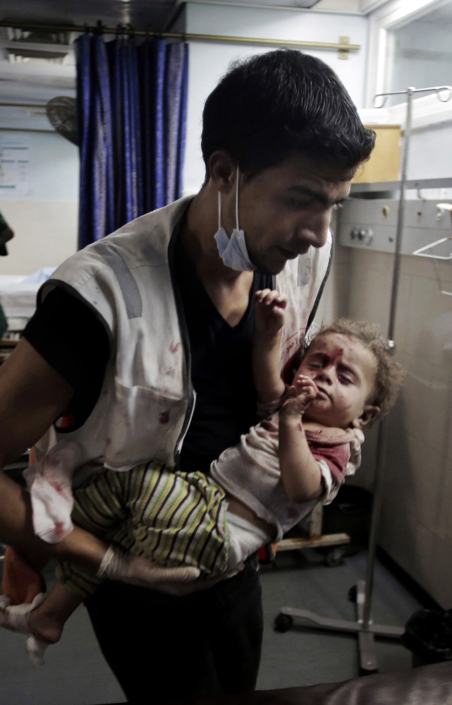 A medic carries a wounded girl in the emergency room of Shifa hospital in Gaza City. About 60 kids have died in a week and a half of fighting.