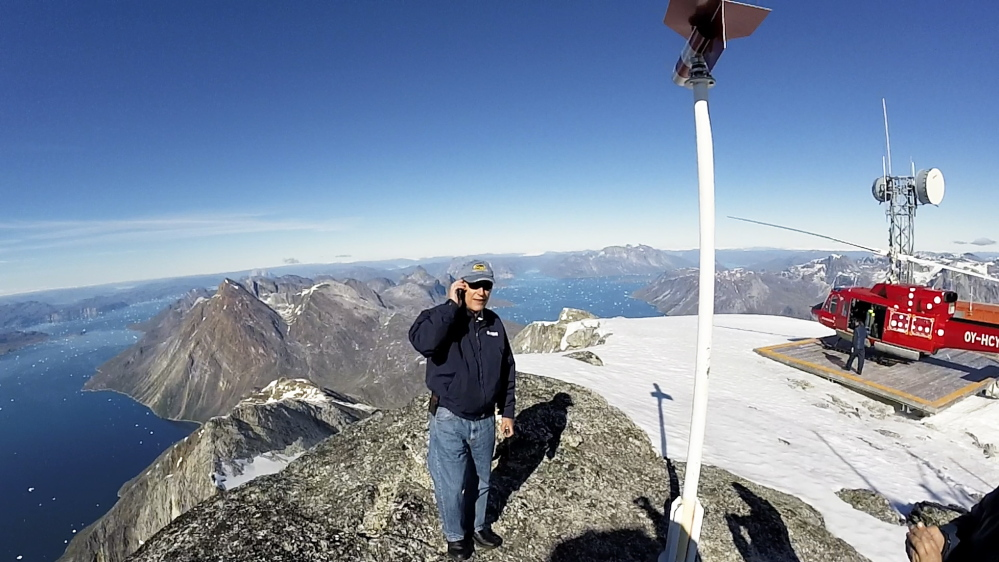 Peter Vigue stands on the top of Mount Qingaq, a 5,300-foot-high mountain peak in southwestern Greenland. From here, one can see valleys where roads will have to be built to access the iron ore mine being developed by London Mining. Frame grab from a video shot by Larus Isfeld, General Manager of Eimskip USA
