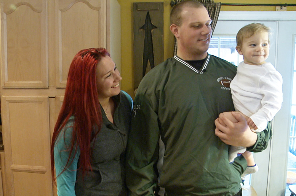 Isaiah Reynolds holds his son, Brody, while standing with his girlfriend, Rachael Tarbox, in a frame grab of a video taken by WCSH in January.
