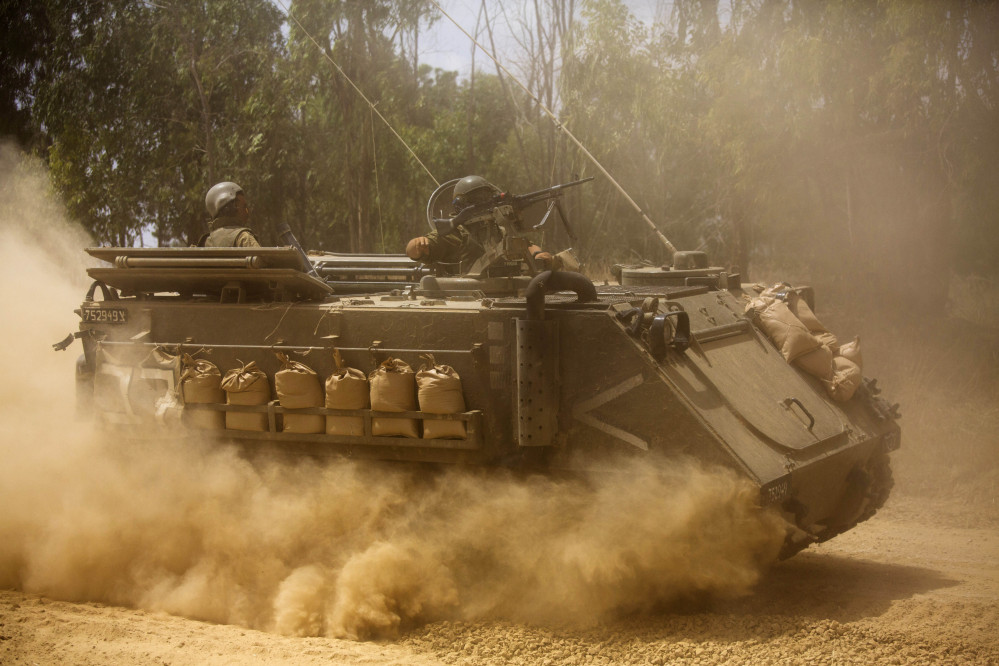 An Israeli armored personnel carrier moves near the Israel and Gaza border on Saturday. Israel pounded Hamas rocket launchers, uncovered more than a dozen cross-border tunnels and engaged in gunbattles with Palestinian militants.