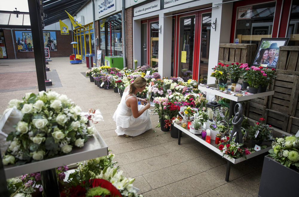 A woman leaves flowers  in Volendam, Netherlands, on Saturday for victims of the crash.