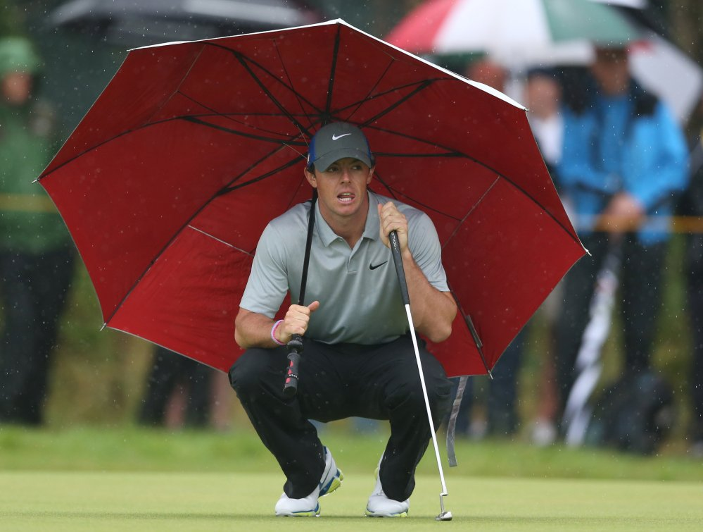 Rory McIlroy kneels under an umbrella as he waits to play on the 4th green Saturday during the third round of the British Open at the Royal Liverpool golf club.