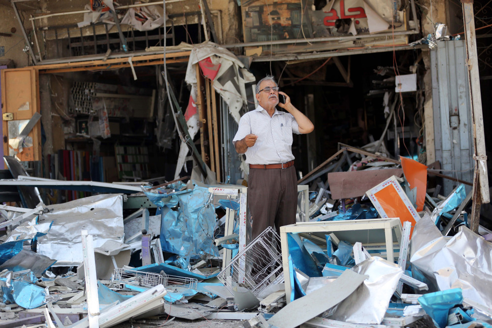 An Iraqi man inspects the site of a bomb attack in the Jihad district in Baghdad on Saturday.