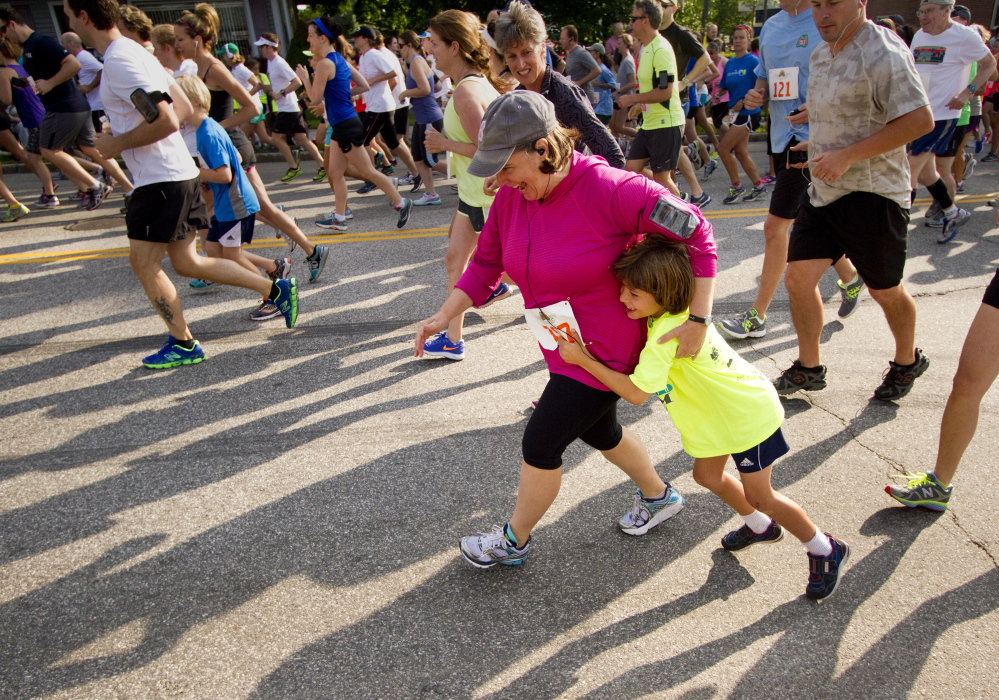 Allison Hodgkins of Yarmouth gets a hug from a young supporter during the start of the 2014 Yarmouth Clam Festival 5 Mile run on Saturday.