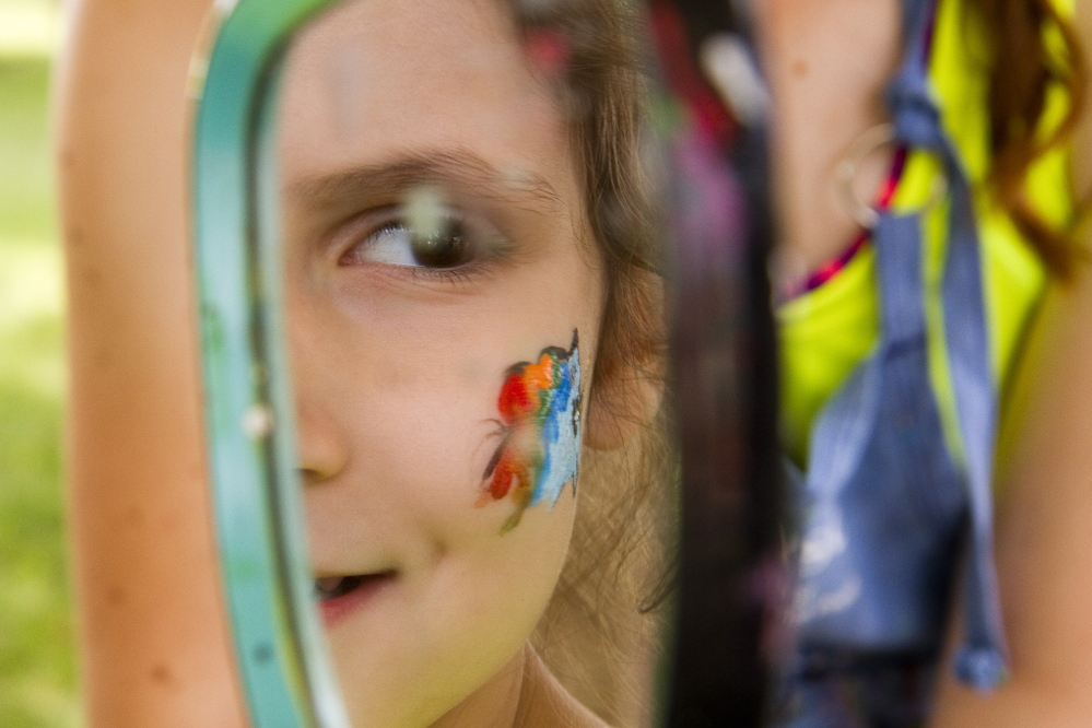Evelyn Braz, 4 of North Yarmouth, looks in the mirror after getting her face painted at the Yarmouth Clam Festival on Saturday.