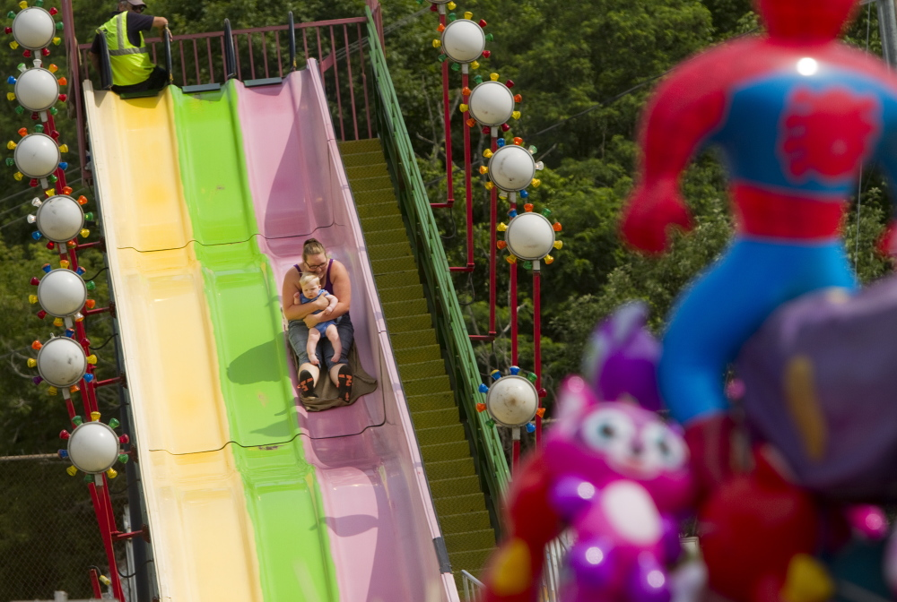 A women and child go down the slide in the amusement area at the Yarmouth Clam Fest in Yarmouth on Saturday.