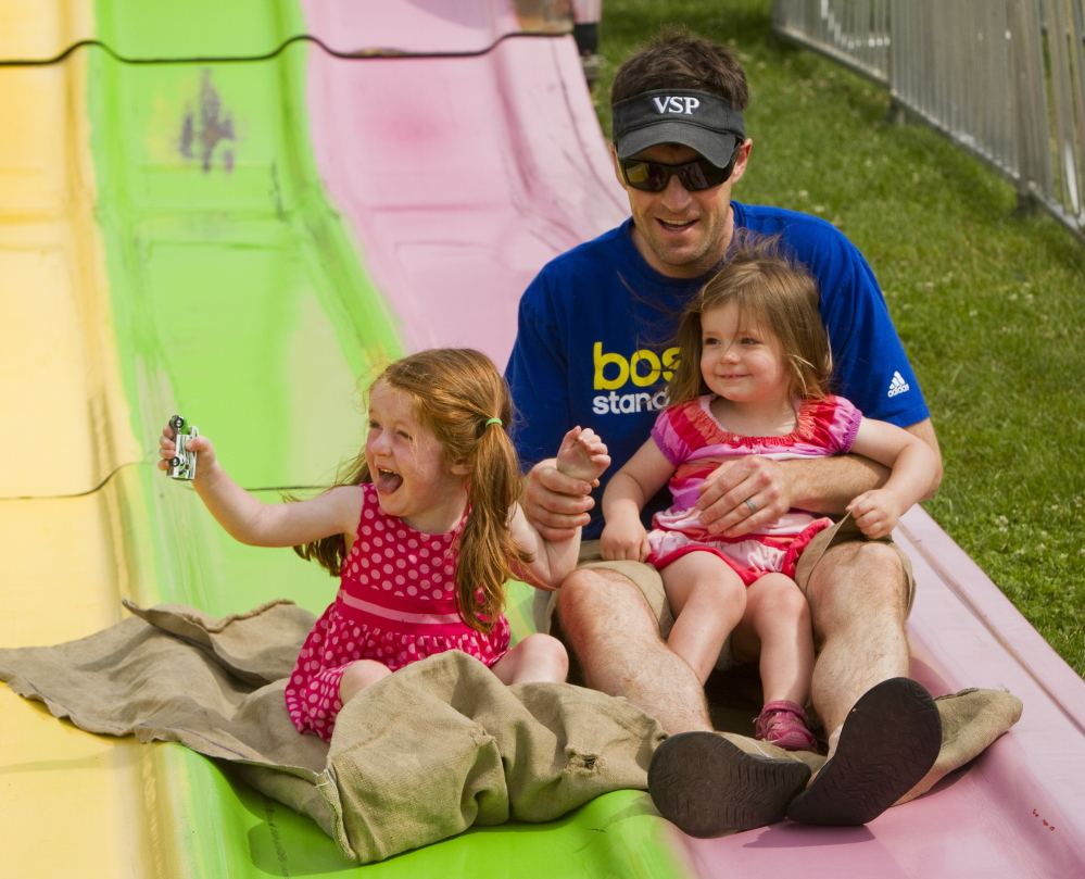 Mackenzie Martin, 3 of Newton, Mass., screams while going down the slide with her father Patrick Martin and sister Emma, 2, at the 2014 Yarmouth Clam Festival in Yarmouth on Saturday.