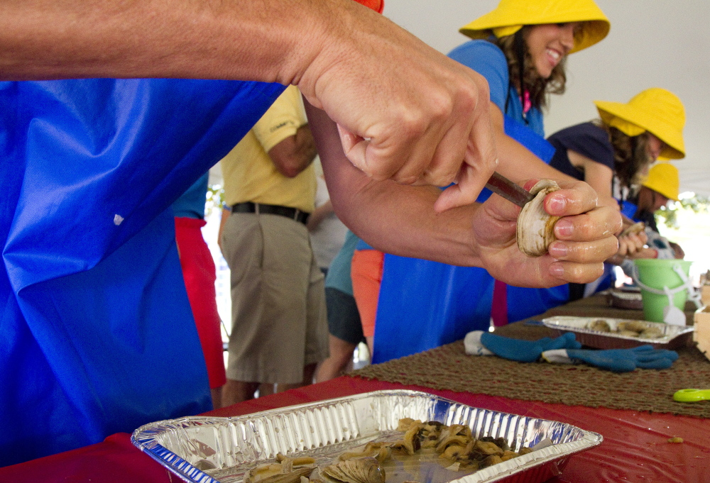 Participants compete in the clam shucking contest at the Yarmouth Clam Festival on Saturday.