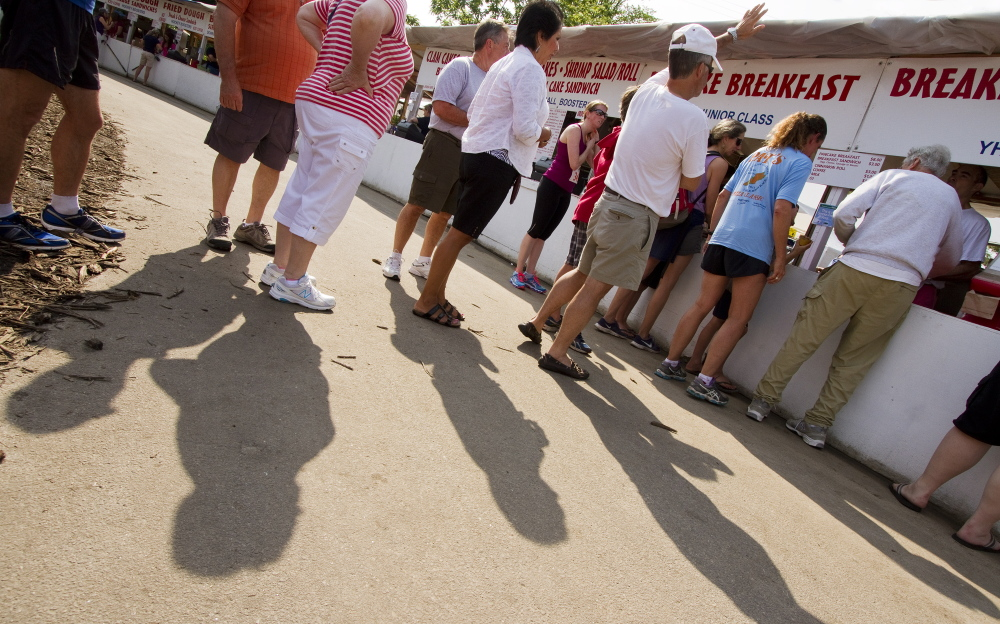 People wait in line for breakfast at the 2014 Yarmouth Clam Festival in Yarmouth on Saturday.