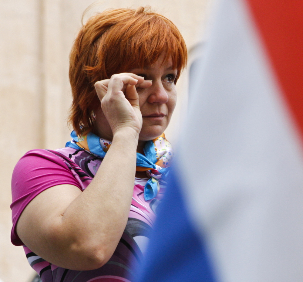 A woman weeps as she looks at flowers and messages left outside the Dutch embassy in Kiev on Saturday.