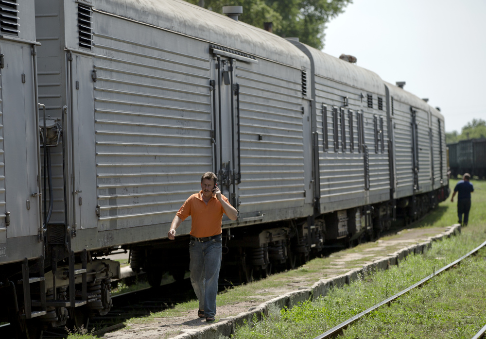 A man speaks on a phone as he walks next to a refrigerated train loaded with the bodies of victims of the Malaysia Airlines Flight 17 crash in Torez, eastern Ukraine on Sunday.