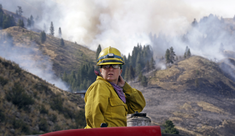 Firefighter Kathleen Calvin looks around as she sits atop her fire truck while waiting to begin work as smoke from a wildfire fills the sky behind on Saturday in Winthrop, Wash.