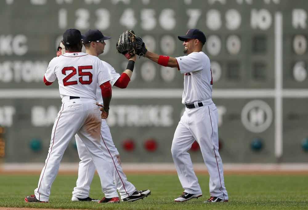 Boston's Jackie Bradley Jr. (25), Daniel Nava, center, and Shane Victorino celebrate after defeating the Kansas City Royals 6-0  in Boston on Sunday.
