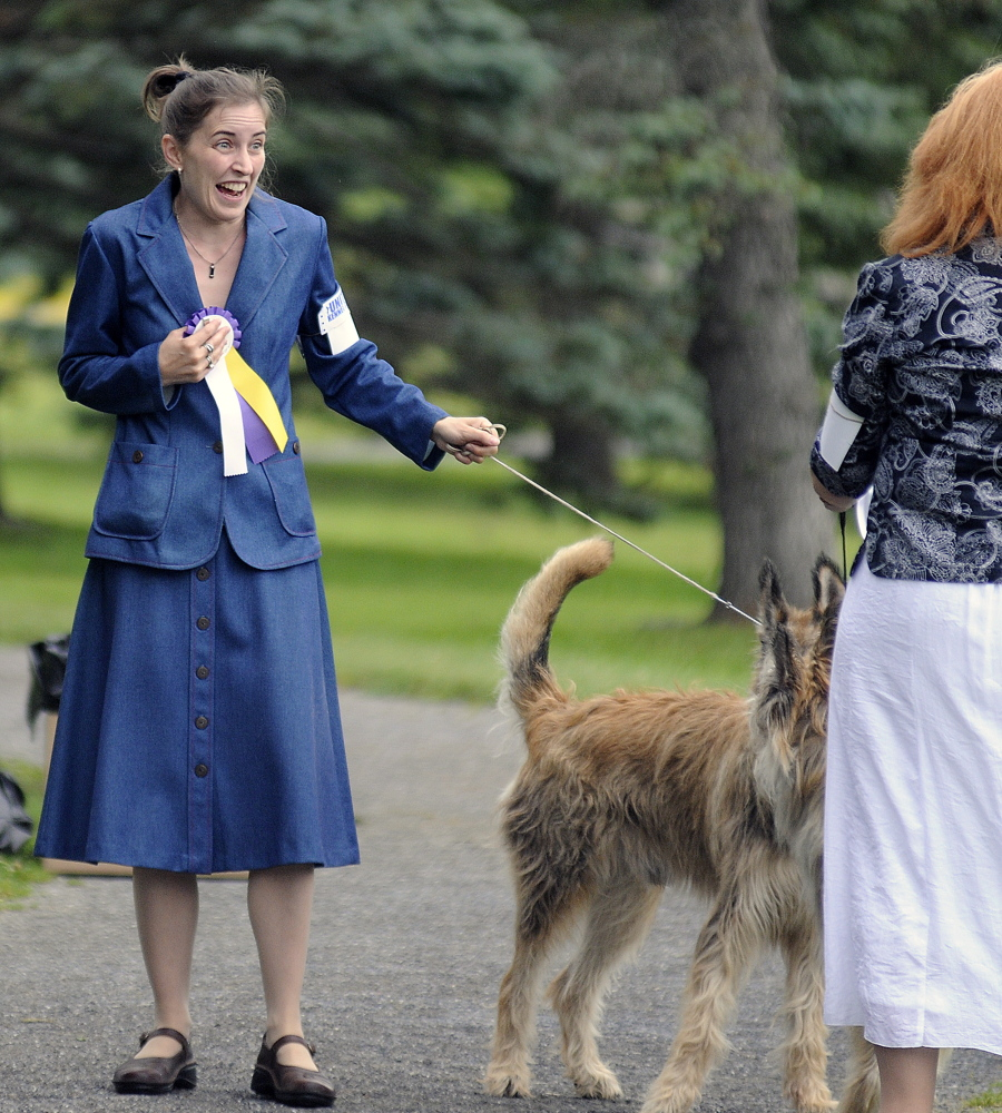 Celestia Lensky of New Hampshire clutches ribbons her dog won in the show Sunday.