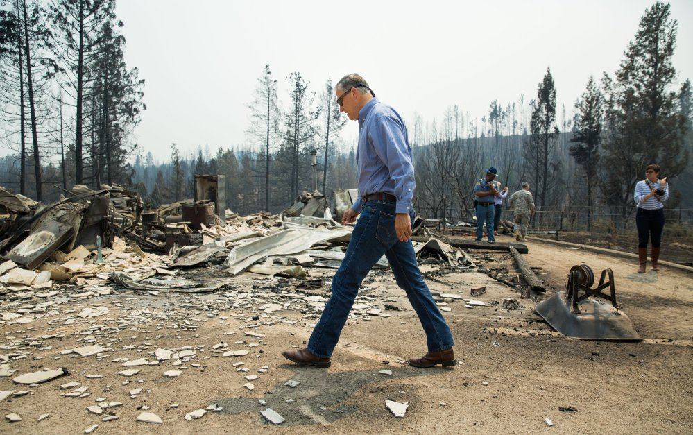 Washington state Gov. Jay Inslee walks the perimeter of a burned-down home during a visit to residential areas affected by the Carlton Complex wildfire near Malott, Wash., on Sunday. The wildfire now covers more than 370 square miles.