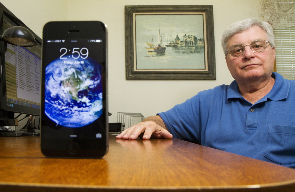 Don Day of Scarborough sits at his desk in his home office. He says poor cellphone coverage is a safety issue and could lower property values because young home buyers lack landlines and need reliable coverage. Carl D. Walsh/Staff Photographer
