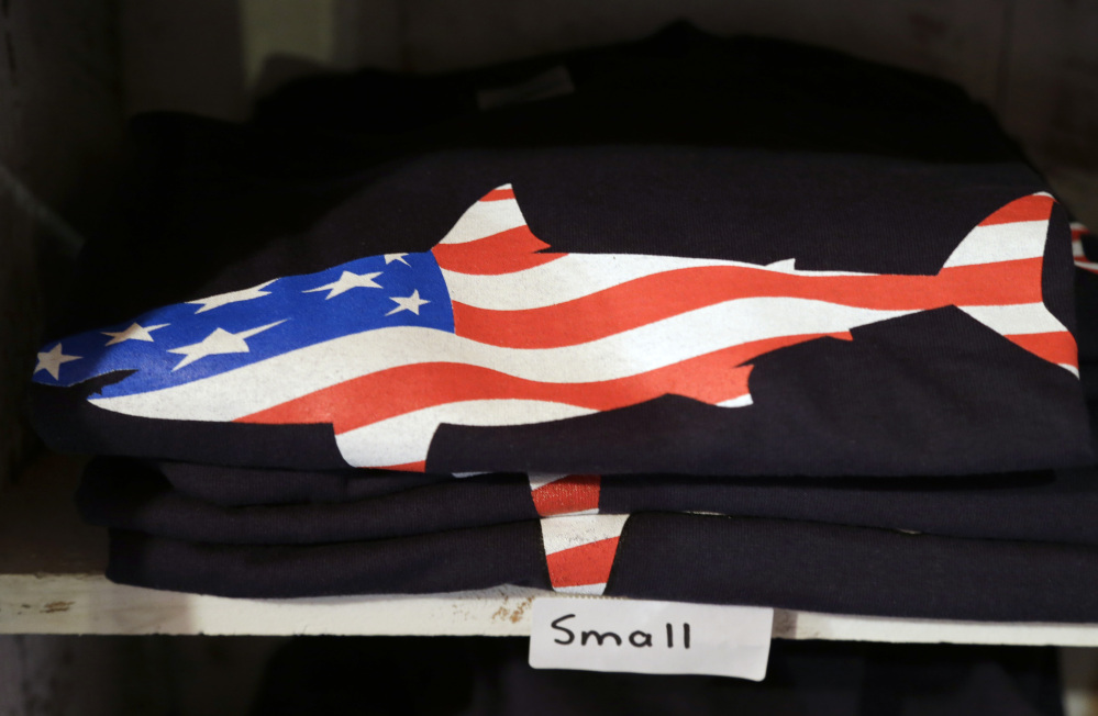 A T-shirt with a likeness of a shark incorporating an American flag rests on a shelf in a souvenir shop in Chatham, Mass.