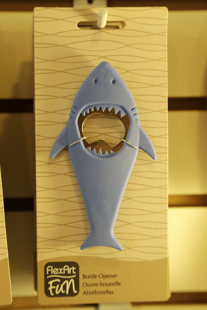 A bottle opener in the likeness of a shark hangs from a hook in a souvenir shop in Chatham, Mass.