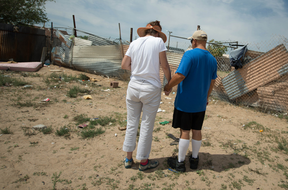 Concerned citizens observe a moment of silence Monday in the field where two homeless men were bludgeoned to death over the weekend in Albuquerque, N.M.