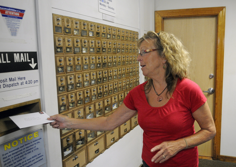 Anne Merrill mails a letter last month at the post office in North Monmouth. The U.S. Postal Service plans to reduce weekday hours there to four hours per day. A public meeting on the plan is scheduled for Tuesday.