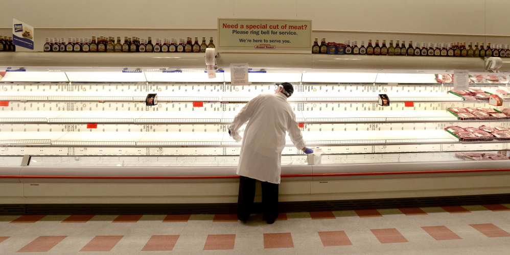 Robert Barclay, a meat department worker at the Market Basket in Biddeford, keeps busy Monday by cleaning the empty shelves usually stocked with chicken products. Workers have protested the firing of a CEO by refusing to make deliveries, leaving stores understocked.