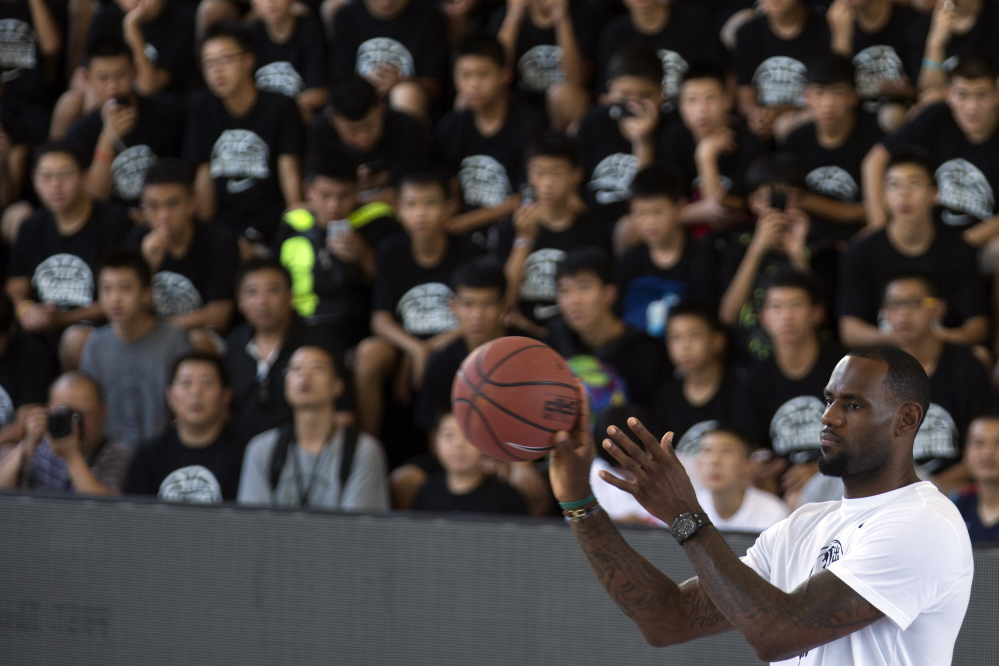 NBA basketball star LeBron James catches a basketball during a Nike-sponsored event in Beijing, China, Monday.