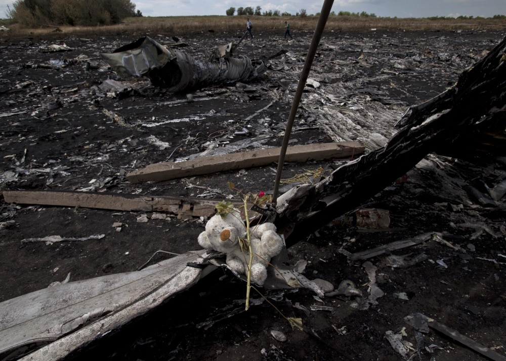 A toy bear is placed on charred plane fuselage parts, as people walk through the crash site of Malaysia Airlines Flight 17 near the village of Hrabove, eastern Ukraine, on Tuesday. A team of Malaysian investigators visited the site along with members of the OSCE mission in Ukraine for the first time since the air crash last week.