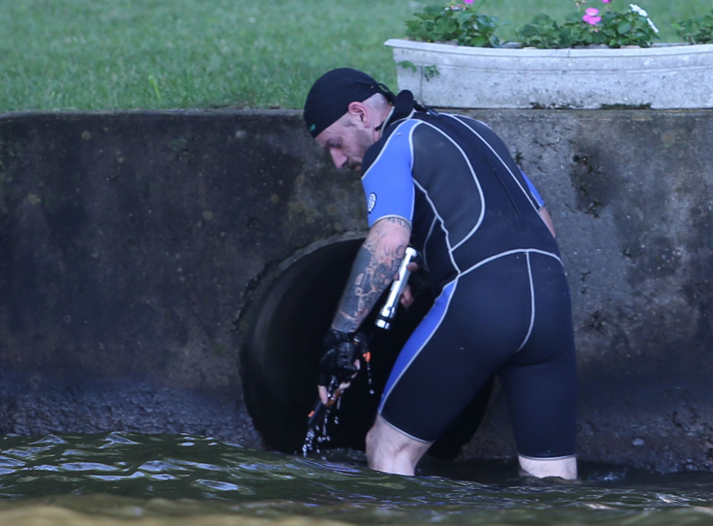 Gerald Andrejcak, assistant director of Common Sense for Animals in Warren County, N.J, searches a large drainage pipe for a large snake in Lake Hopatcong near Jefferson, N.J. Associated Press photos