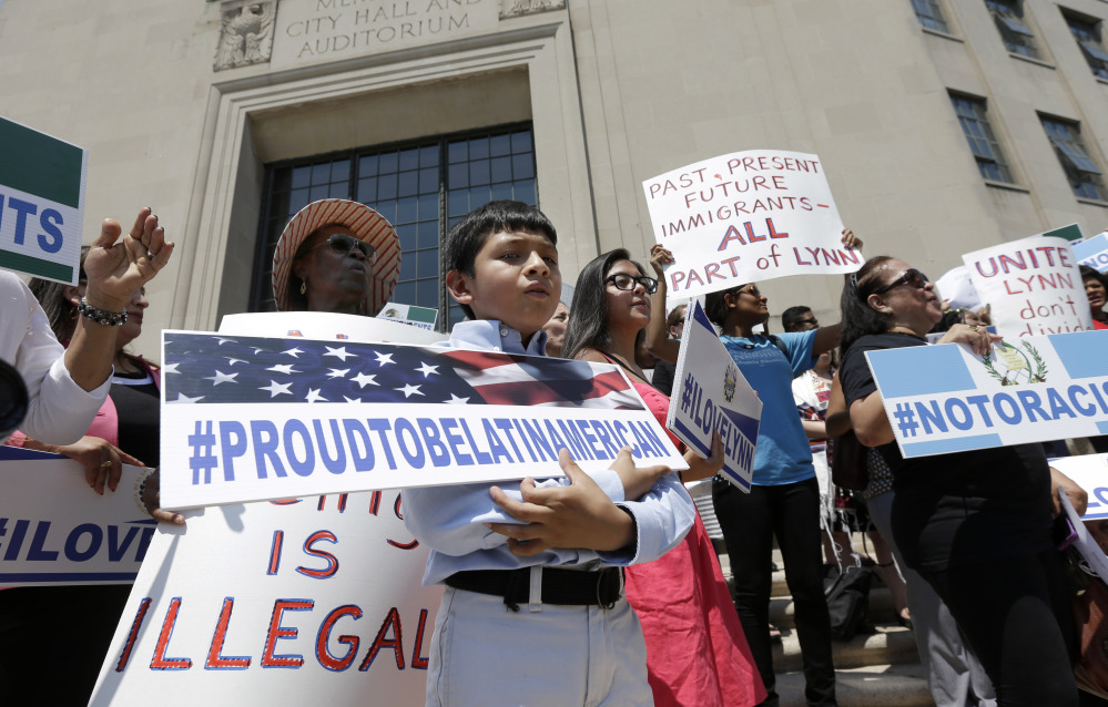 Christian Gonzalez, 9, of Lynn, Mass., displays a placard during a rally Tuesday on the steps of City Hall in Lynn, held to protest what organizers describe as the scapegoating of immigrants for problems in the city. Education officials complain their schools are being overwhelmed by young Guatemalans who speak neither English nor Spanish. Gonzalez, a U.S. citizen, was born in Boston.