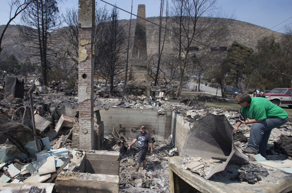 Jake Hixon, center and Kathy Harding look for family heirlooms they may have been spared at a relative's house Monday after the fire that swept through Pateros, Wash.