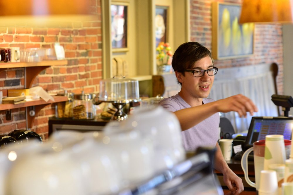 "Christopher McClure, 26, of Portland works as a barista Tuesday at Arabica Coffee, where he makes $10 an hour. He favors an increase in the city's minimum wage. ""For people in my situation ... I just don't see how they can get by,"" he said."