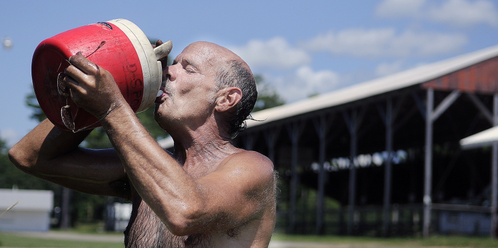 Carnival worker Bill Derick cools off with water Monday while setting up rides at the Pittston Fairgrounds.