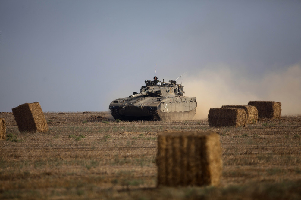 An Israeli tank runs between hay bales near the Israel and Gaza border Wednesday. Israeli troops battled Hamas militants near a southern Gaza Strip town, sending Palestinian residents fleeing.