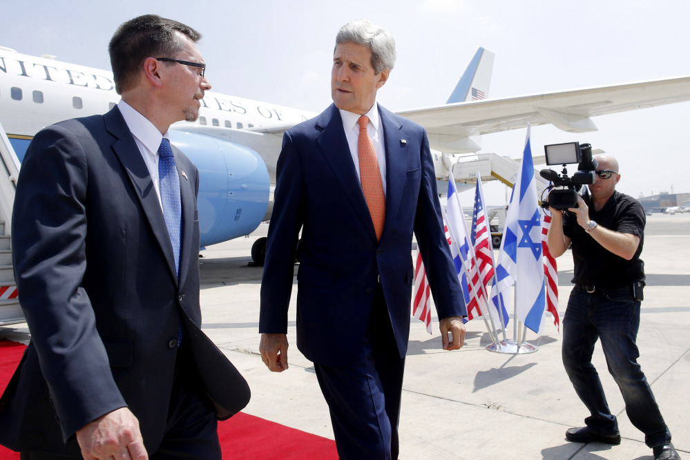U.S. Secretary of State John Kerry walks with U.S. Embassy Deputy Chief of Mission Bill Grant as he arrives to Tel Aviv Wednesday, July 23, 2014. Kerry is meeting with U.N. Secretary-General Ban Ki-moon, Israeli Prime Minister Benjamin Netanyahu, and Palestinian Authority President Mahmoud Abbas as efforts for a cease-fire between Hamas and Israel continue.