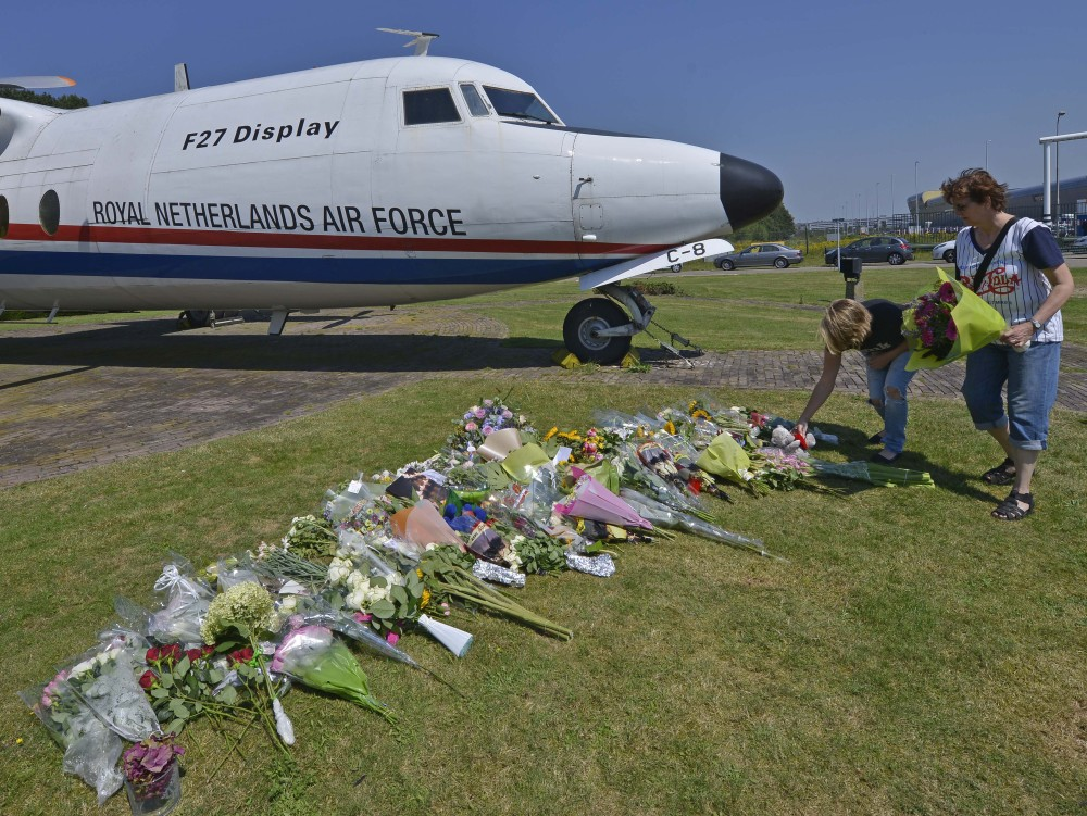 People lay flowers in front of a plane prior a ceremony to mark the return of the first bodies, of passengers and crew killed in the downing of Malaysia Airlines Flight 17, from Ukraine at Eindhoven military air base, Wednesday.
