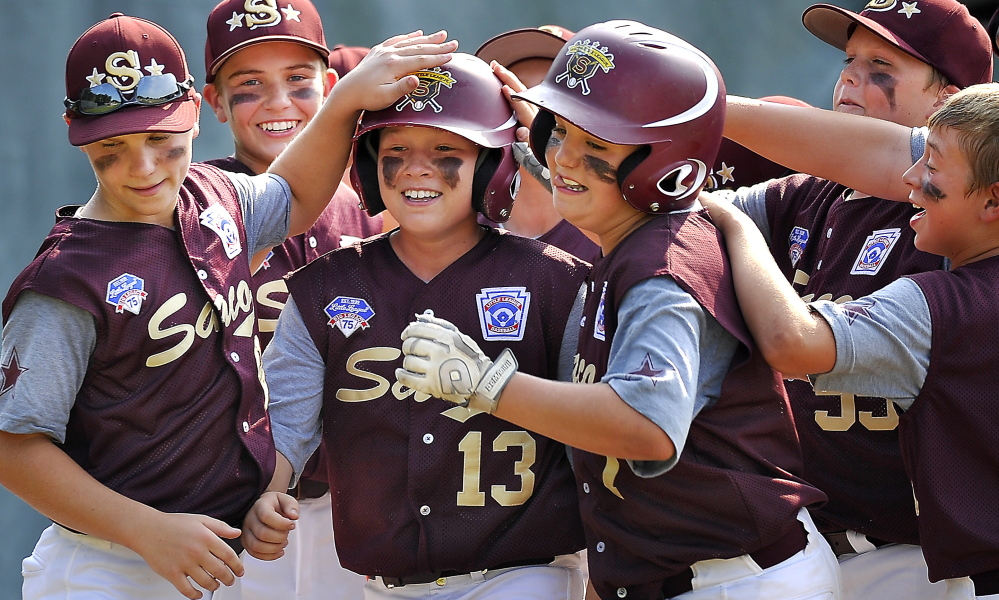Saco Maremont's Ben Ham, center, gets mobbed by his teammates after hitting the second of three straight home runs by the team in a Little League state tournament game.