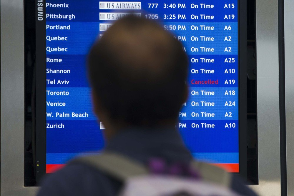 A traveler views a departures board Tuesday at the Philadelphia International Airport after the Federal Aviation Administration had told U.S. airlines they were prohibited from flying to Tel Aviv after a Hamas rocket exploded nearby.