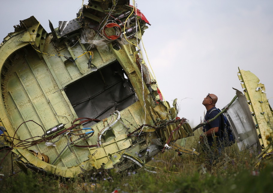 An official inspects a piece of the Malaysia Airlines plane shot down in Ukraine. It was one of three tragedies in a harrowing week for air travel.