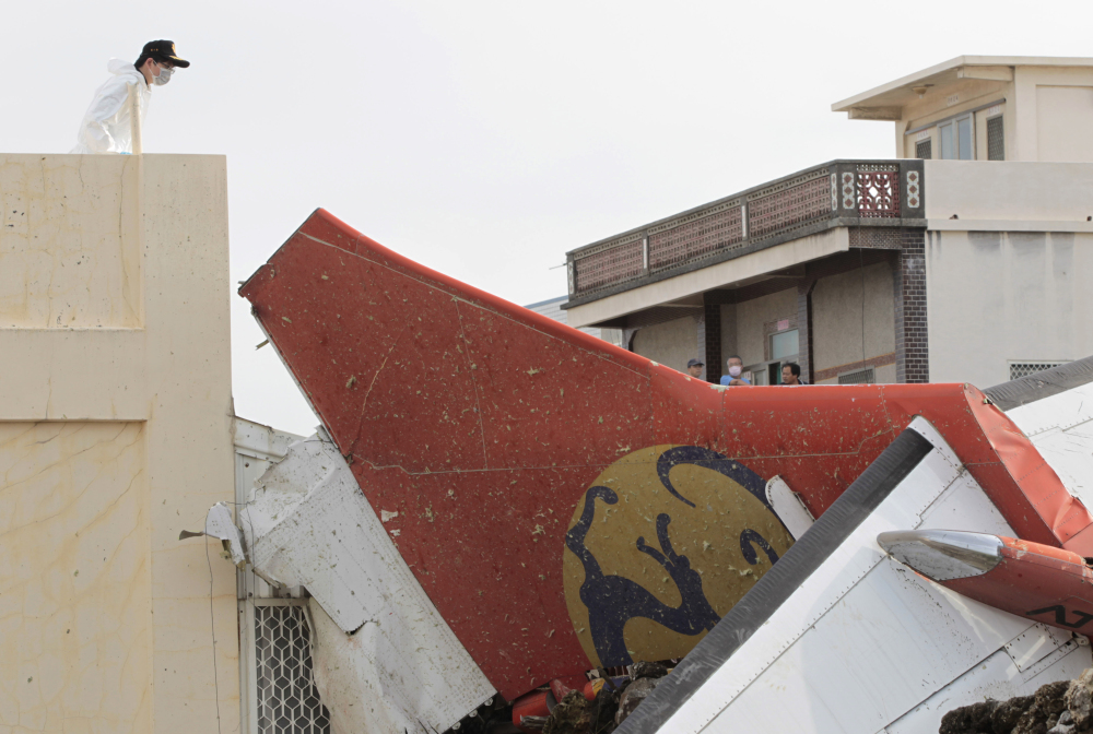 A special investigator inspects the tail of crashed TransAsia Airways flight GE222 on the outlying island of Penghu, Taiwan, on Thursday. Stormy weather on the trailing edge of Typhoon Matmo was the likely cause of the plane crash that killed more than 40 people, the airline said Thursday.
