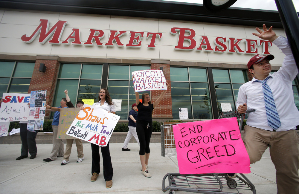 Market Basket employees Rees Gemmell, far right, and colleagues acknowledge passing supporters as they picket in front of the supermarket Thursday in Haverhill, Mass., on July 25.