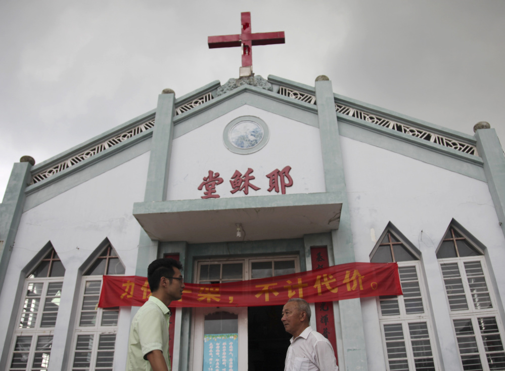 "Pastor Tao Chongyin, left, speaks with Fan Liang'an in front of the Wuxi Christian Church in Longwan, Wenzhou, in eastern China's Zhejiang province. ""I won't let them take down the cross even if it means they would shoot me dead,"" said Liang'an."