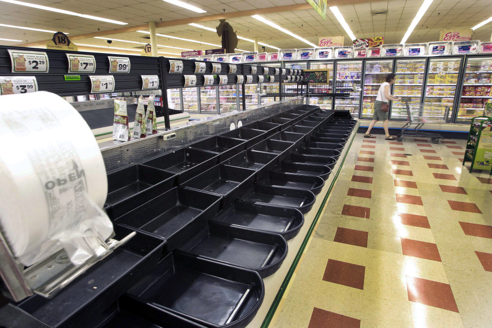 A customer walks by the empty produce aisle Thursday at a Market Basket in Concord, N.H. The Associated Press