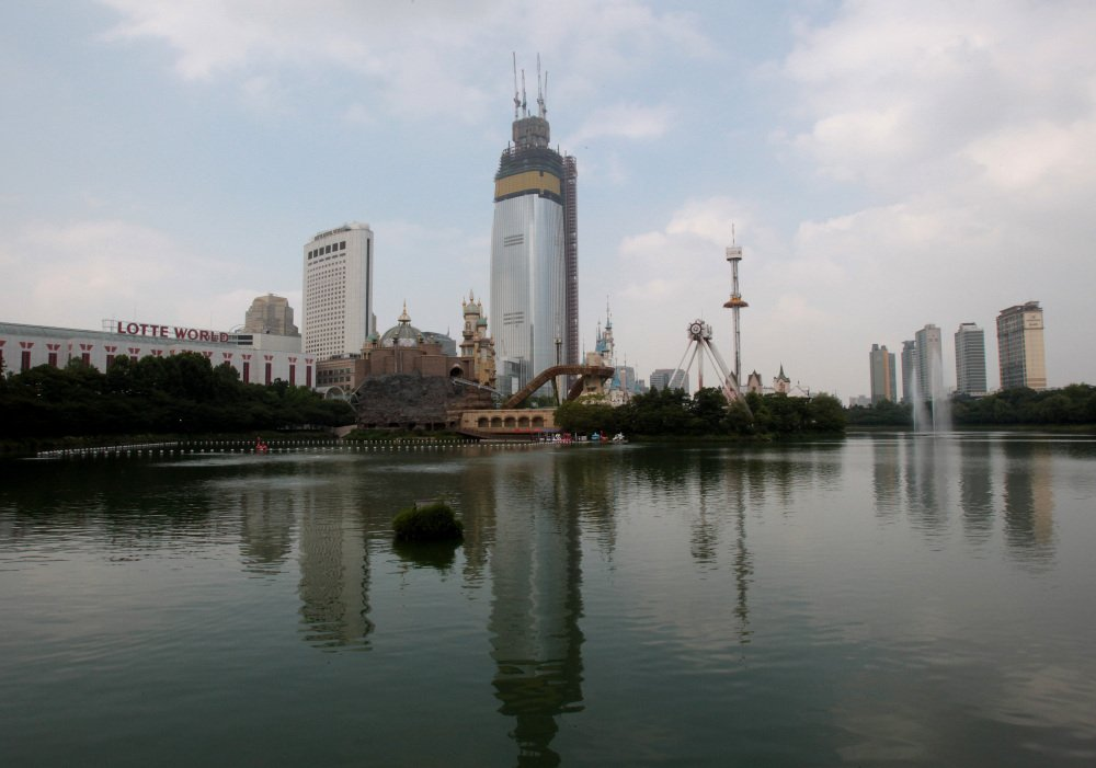 "The Lotte World Tower is under construction near Seokchon Lake in Seoul, South Korea, this month. Problems such as falling lake levels and sinkholes in residential neighborhoods have led to an official review of the project, reassessing an ethos of ""progress first, safety last"" that was largely unquestioned as the country rapidly industrialized."