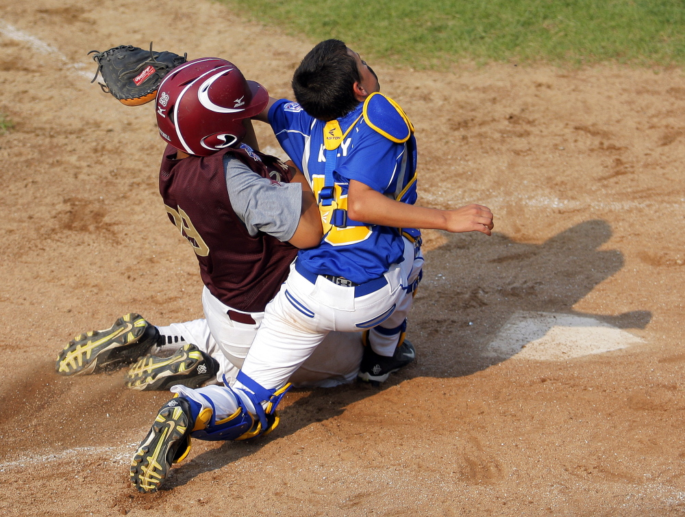 Will Mitchell of Saco barrels into Falmouth catcher Ike Kiely during the Little League state championship game in Biddeford. Mitchell was called safe, but Falmouth won 13-10, preventing Saco from winning the state championship for the second straight year. Gabe Souza/Staff Photographer