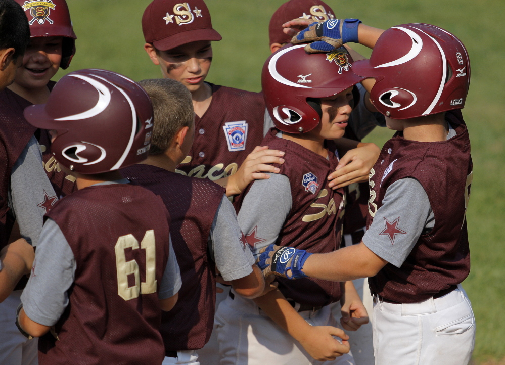 Hayden Lehigh, at right, and other teammates congratulate Ben Ham on his home run during the Little League state championship game  in Biddeford on Friday. Gabe Souza/Staff Photographer