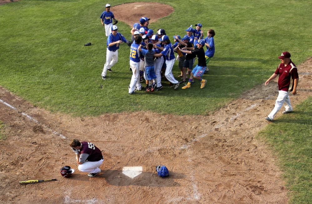As Falmouth celebrates winning the Little League state title at top right, Saco's Patrick Sawyer, bottom left, buries his head in his hands. Gabe Souza/Staff Photographer