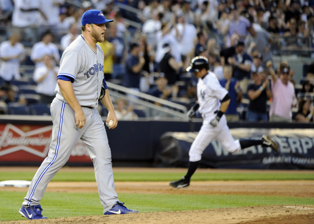Toronto's Mark Buehrle shows frustration as New York's  Ichiro Suzuki, right, rounds the bases with a third-inning three-run homer during the Yankees' victory Friday night.
