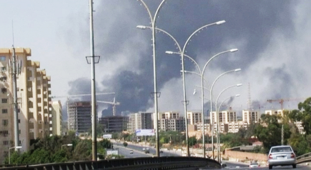 In this Sunday, July 13, 2014 file image made from video by The Associated Press, smoke rises from the direction of Tripoli airport in Tripoli, Libya.