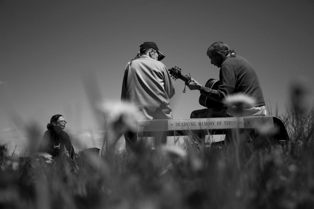 "Melissa Altvater, left, and her father, Dave Homan, center, listen as tribal elder Allen Sockabasin plays guitar near the water at Pleasant Point in Washington County. Sockabasin is a longtime champion of the Passamaquoddy language, ""the key to open the lock of independence for native people."""