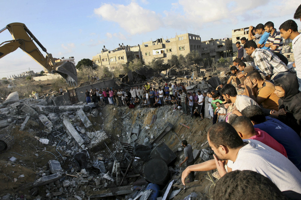 Palestinians gather around the rubble of a building where at least 20 members of the Al Najar extended family were killed by an Israeli strike in Khan Younis, in the southern Gaza Strip, Saturday.